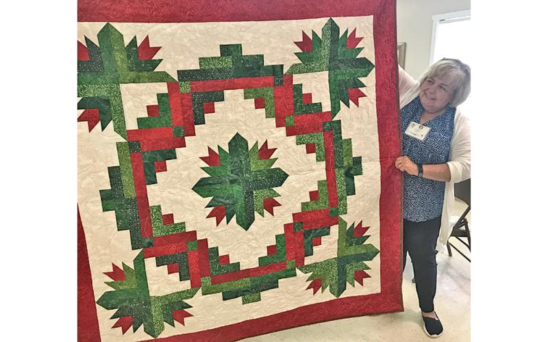 Lynda Duke stands beside the Christmas quilt that will be raffled off Friday, July 26 at The Common Thread. The raffle is part of the shop's Christmas in July Quilt Show, free and open to the public. Raffle tickets are $5 and proceeds go to support the Dahlonega Valor Quilters, who provide quilts to Lumpkin County's veterans as a thank you for their service.