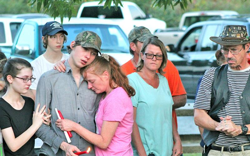 Austin Bender holds a candle in honor of his sister as he consoles his mother Carol Gillreath at last week's vigil on Lake Zwerner.
