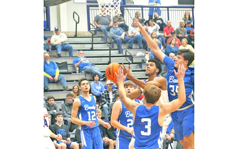 Indians scoring standout Pat Jackson flies through traffic to the basket for two of his 15 points in Lumpkin's loss to eighth-ranked Banks County at the Longhouse last week.
