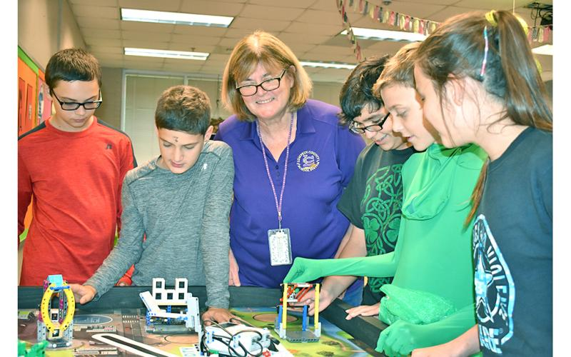 Lumpkin County's School System Teacher of the Year, Tori Jones, oversees student members of an after-school group doing what Jones believes to be the key to education—hands-on learning. They are members of the Middle School's FIRST LEGO League Team working (on Halloween) to build robots to accomplish a real-world task. From left are Jon Gooby, Samuel Fuerstenberg, Jones, Cameron Allison, Nathan Berzack and KayLeigh Zahn. The students will compete with other FIRST LEGO League teams Nov. 23—their first year t