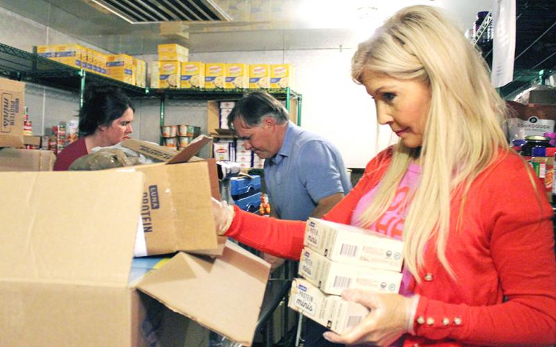 Debra Stipe helps pack one of nearly 80 boxes sent out by Lumpkin County Family Connection's Backpack Buddies program last week.