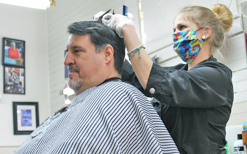 Mark Evans arrived early on Monday morning to get his first post-quarantine haircut at Woody's Barbershop. Mandi Borland was one of only two barbers to work the first day the barbershop was re-opened.