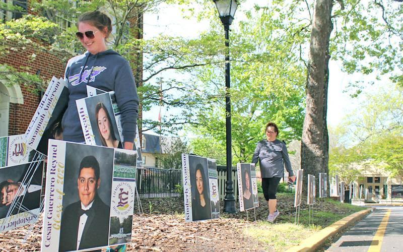 Lumpkin County High School assistant principal Whittney McPherson carries senior signs as she and other LCHS faculty members placed the signs along downtown Dahlonega to honor the Class of 2020.