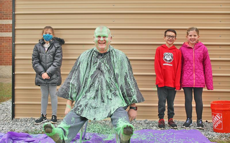 Long Branch SRO Nick Parrish was slimed in celebration of exceeding the school's original fundraising goal, much to the pleasure of LBES students (from left) Ellie Flynt, Micah Smith and Briley Seabolt.