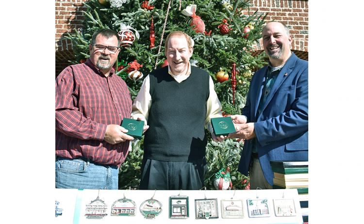 Local philanthropist and merchant Thomas Scanlin (center) spent a little time recently playing Santa to the community, gifting both Lumpkin County and the City of Dahlonega with complete sets of the Community Helping Place Official Dahlonega Christmas Ornament. Scanlin said he hopes the sets will be on permanent public display for all to enjoy. Accepting the gifts are (left) Lumpkin County BOC Chairman Chris Dockery and Dahlonega Mayor Sam Norton.
