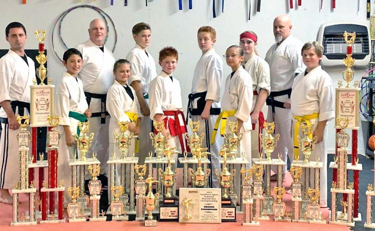Local karate competitors pictured (from left): Travis Hamner (instructor), Christopher Frausto, Brad Bowelle (chief instructor, owner), Ella Greene, Owen Mondell, Aiden Marshall, Austin Marshall, Lindsey Greene, Alexis Weir, Wayne Marshall (instructor) and Josiah Payne. Not pictured: Jameson Ballard, Nathan Voci, Tyler Voci and Luke Scheinoha.