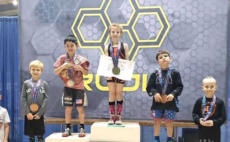 Allie Procter stands on top of the podium after winning her third straight Youth Georgia Wrestling State Championship title recently. Procter, 8, racked up three wins by pin versus her male opponents to secure her third straight championship title.