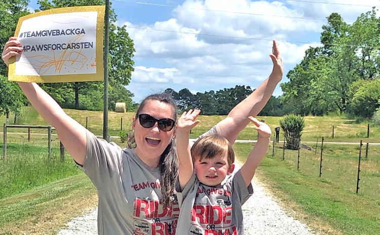 Team Give Back member Mallory Wilkins and her son Bo finish up the virtual fundraiser for Carsten Ussery.