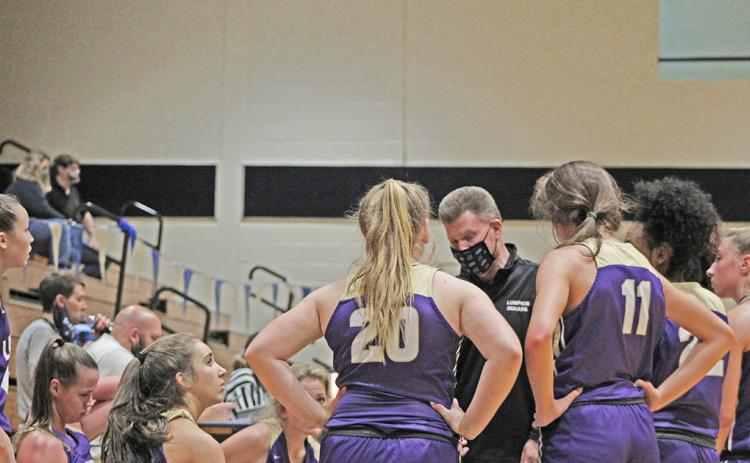 Head basketball coach David Dowse huddles with his team during a timeout in Lumpkin County's 99-20 win over West Hall.