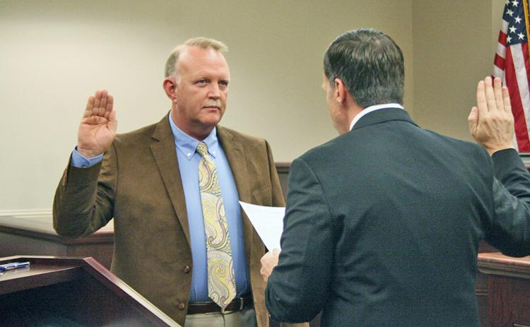 New Lumpkin County Magistrate Court associate judge Jim Sheppard is shown swearing in as the county coroner.